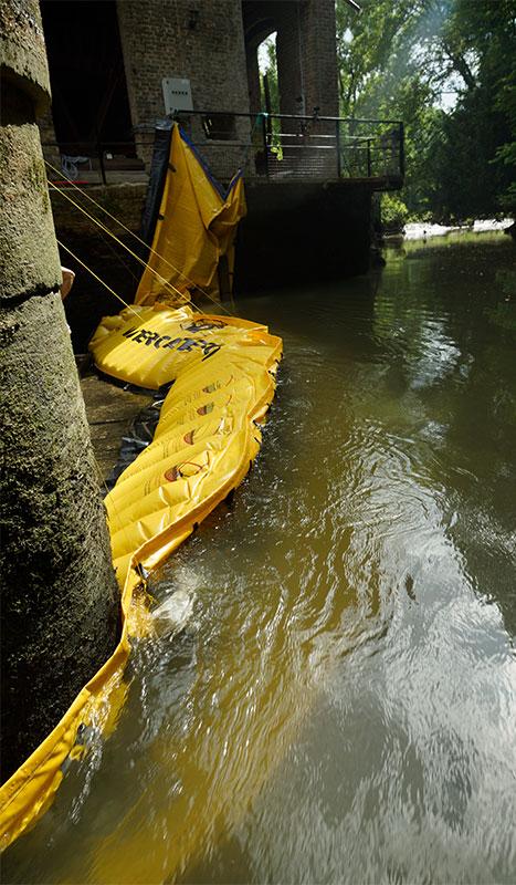 """"""" Flexibele Water-Gate © WA-2850 kofferdam in L. Steun op een muur van de molen op de linkeroever en op een stapel van een wannenbrug in het midden van de rivier."""""""