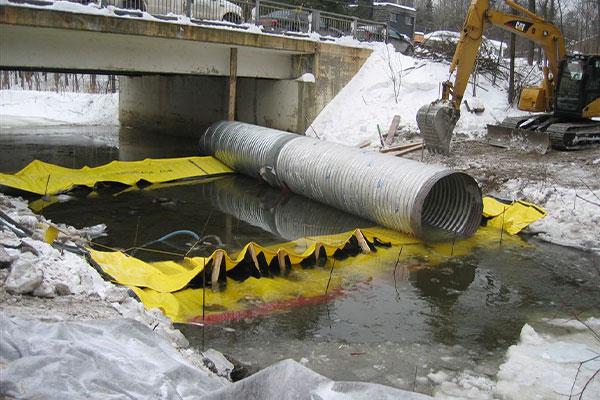 Installatie van twee Water-Gate © kofferdammen kop aan staart met bypass buis geplaatst op de flexibele dammen.